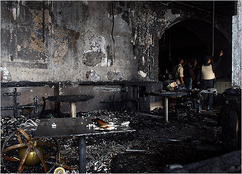 Security officials survey a destroyed room inside the Taj Mahal Palace & Tower Hotel after the armed siege on November 29, 2008 in Mumbai, India. Indian officials have declared the siege at the Taj hotel over as the remaining militants were killed when commandos stormed the building. The city of Mumbai was rocked by multiple coordinated terrorist attacks that targeted locations popular with foreigners, late on November 26, killing at least 195 people.  (Photo by Julian Herbert/Getty Images)