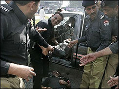 Pakistani police officer gather around the dead body of a police commando at the shooting site in Lahore, Pakistan on March, 3, 2009. (AP Photo/K.M. Chaudhry)