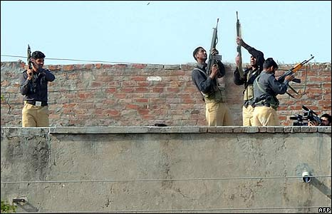 Pakistani security forces fire into the air from the roof of a police academy near Lahore to celebrate the end of a siege that lasted several hours.